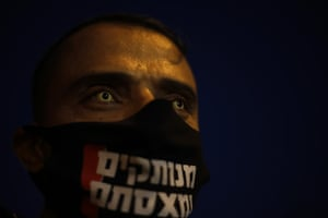 """A protester wears a face mask to protect against the coronavirus that reads """"you are disconnected we are fed up"""" during the protest"""