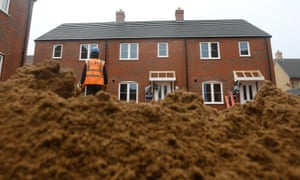 Construction workers lay a driveway at a Persimmon construction site