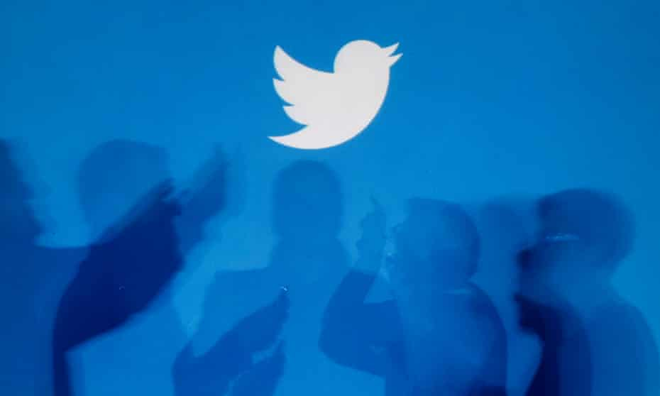 Shadows of people holding mobile phones are cast onto a backdrop projected with the Twitter logo