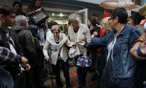 People help a voter at the Escola de la Concepció in Barcelona.