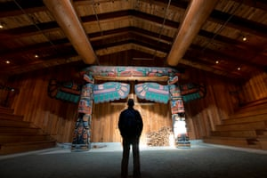Man stands in a spotlight area in a large wooden structure in Klemtu, British Columbia. The Kitasoo/Xai'xais of Klemtu are a remote First Nations community accessible only by water or air. This is the village's big house, where traditional ceremonies take place.