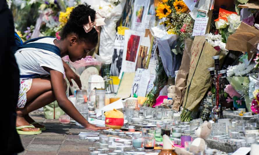 A child places a candle amongst floral tributes close to Grenfell Tower.