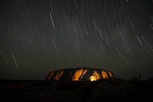 A long exposure photograph shows star trails over Uluru in October
