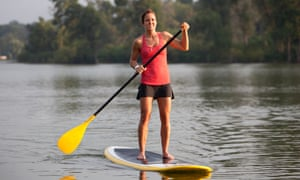 Woman paddleboarding on a calm lake.