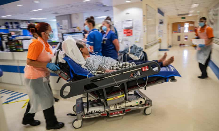Medical staff transporting new suspected a patient to a hospital ward in England