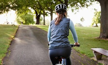 Woman cycling at a park.