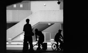 Anonymous teenagers in silhouette in a concrete high rise estate