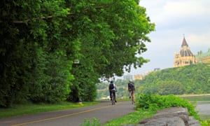 Cyclists riding along the scenic cycle path with Parliament Hill in Ottawa in the background.