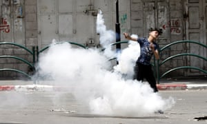 A Palestinian throws back a tear gas grenade against Israeli troops during clashes in the West Bank city of Hebron