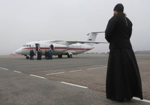 An Orthodox priest watches as the bodies of the crash victims arrive in St Petersburg.