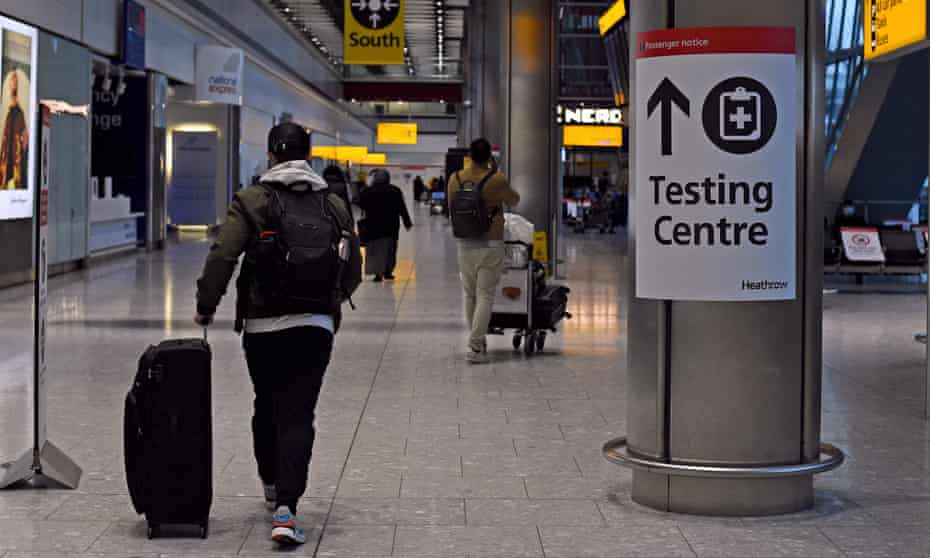 A passenger walks past a sign for the Covid testing centre at London's Heathrow airport