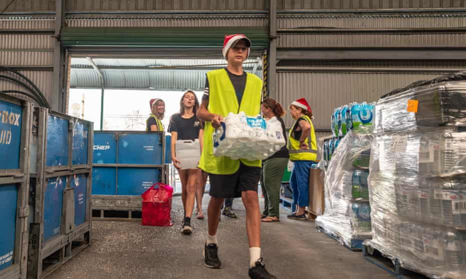 A volunteer at Granite Belt Water Relief helps a Stanthorpe family carry drinking water to their car