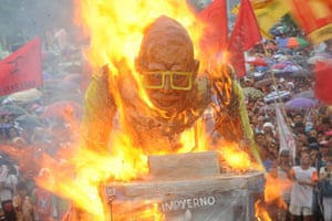Manila, Philippines Protesters burn an effigy of President Benigno Aquino after they are blocked by police marching towards Batasang Pambansa, where Aquino will address the joint session of Congress