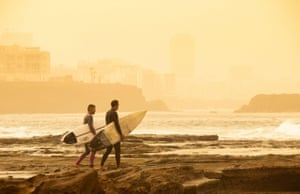 Surfers head into the sea as one of the worst Saharan dust storms in recent years reduces visibility to 400 metres in Las Palmas, Canary Islands, Spain