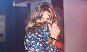 feist covering the lower half of her face with her jacket in a posed press shot