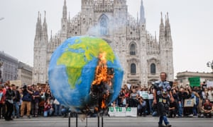 Students set fire to a model of the Earth during a climate change protest in Milan