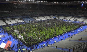 Spectators gather on the pitch of the Stade de France after explosions outside the stadium in November.