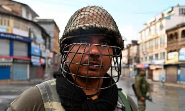 Indian security personnel wear helmets when patrolling Srinagar streets.