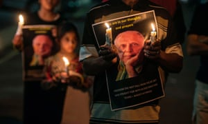 People hold candles as they gather for a night vigil to pray for Kathrada