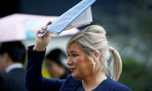 Sinn Feinn's leader in Northern Ireland, Michelle O'Neill, shields herself from the rain while speaking to journalist outside the Houses of Parliament in Westminster.