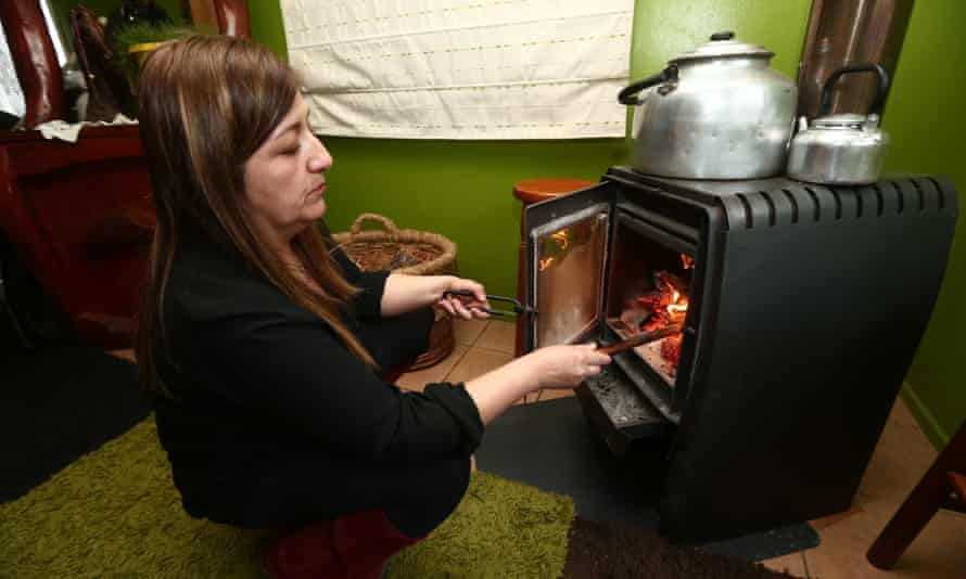 Yasna Seguel puts wood in the fire at her home.