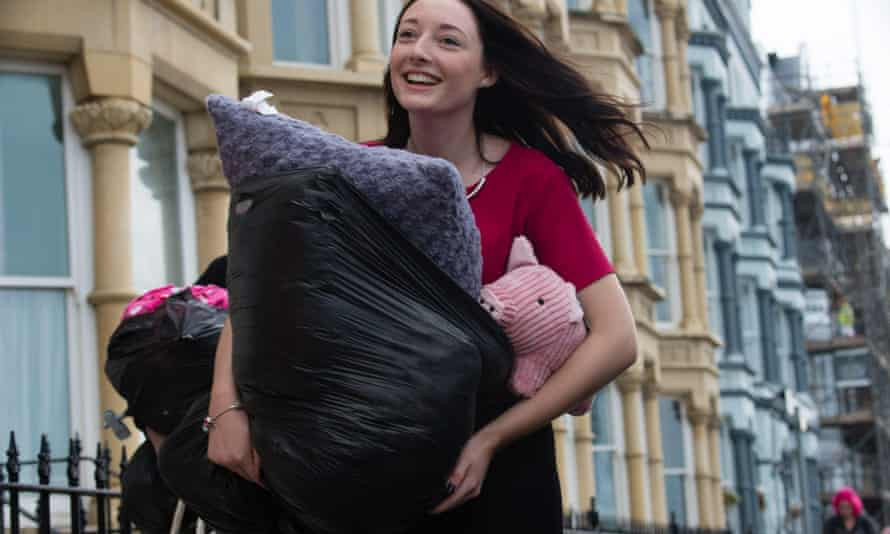 A happy smiling first year 'fresher' woman student arrives at her halls of residence in Aberystwyth