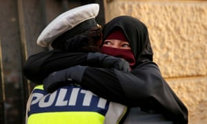 Ayah, a niqab wearer weeps as she is embraced by a police officer during a demonstration against the Danish face veil ban in Copenhagen.