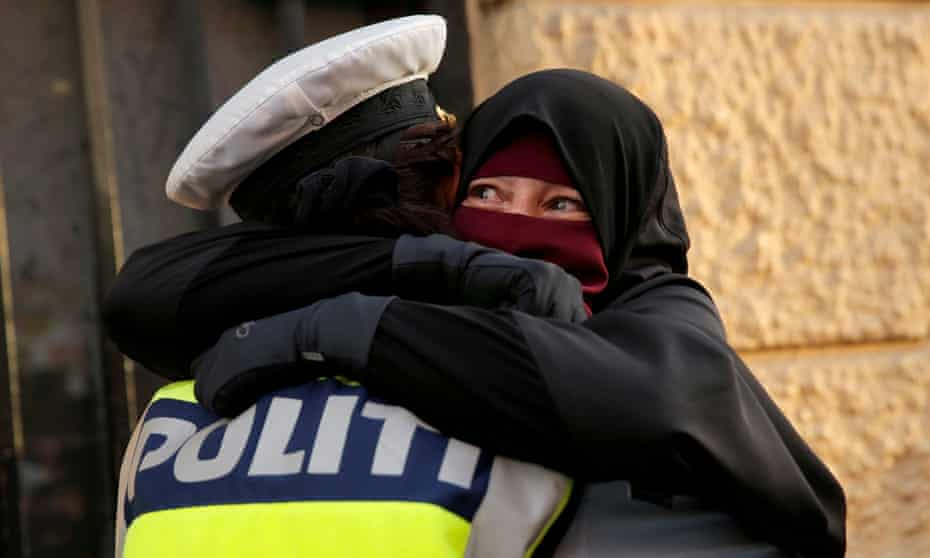 Ayah, a niqab wearer, and a policeman embrace at a protest