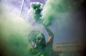 A woman waves a green flare during a demonstration to demand greater rights for women, in front of the National Congress, in Santo Domingo, Dominican Republic