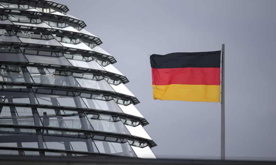 Germany flag next to the dome of the Reichstag building
