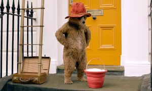 Paddington Bear, in his red hat, stands on the doorstep of his new home, hands on hips, looking down at a red bucket