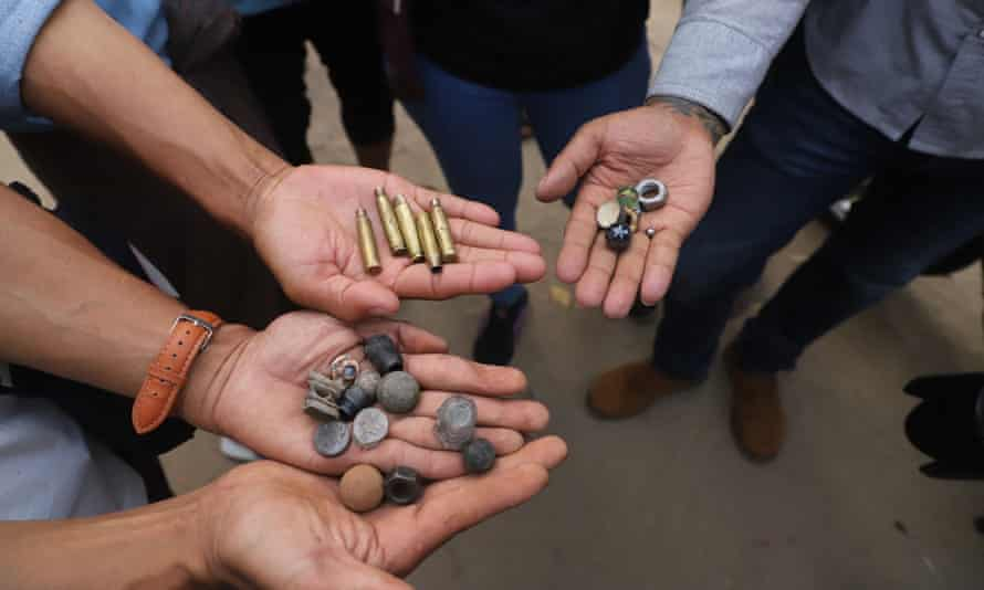 Protesters hold out bullet cartridges