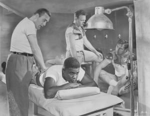 Jackie Robinson receives a back massage in the locker room while his team-mates suit up.
