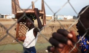 Bentiu, South SudanAn internally displaced girl carries a chair at a UN Protection of Civilians site