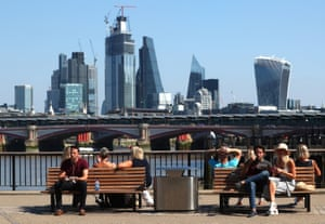 People sit by the River Thames with the financial district in the background.