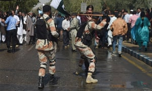 Pakistani paramilitary officers move towards protesters outside the PIA offices near Karachi airport