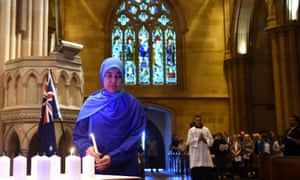 Maha Abdo, of the Muslim Women's Association, lights a candle for the victims and those affected by the terrorist attacks in Paris during a mass at St Mary's cathedral on Monday.