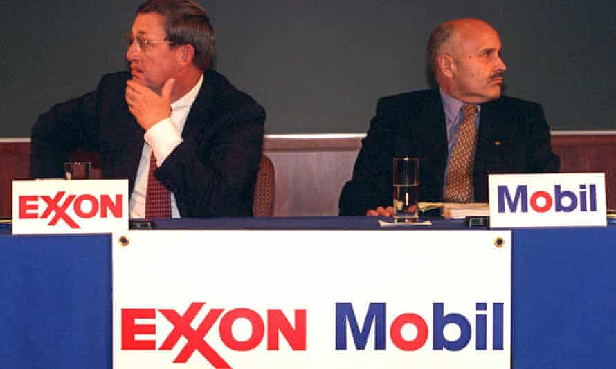 Lee Raymond, chairman of Exxon Corp., left, and Lucio Noto, chairman of Mobil Corp., look in opposite directions during the news conference to announce the merger of their companies Tuesday, Dec. 1, 1998, in New York.