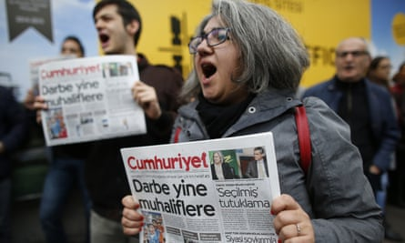 Protesters shout slogans as they hold the latest copy of Cumhuriyet outside its headquarters