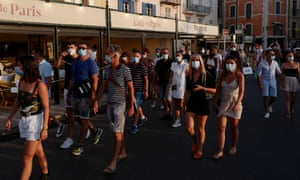 People in face masks at St-Tropez harbour in southern France