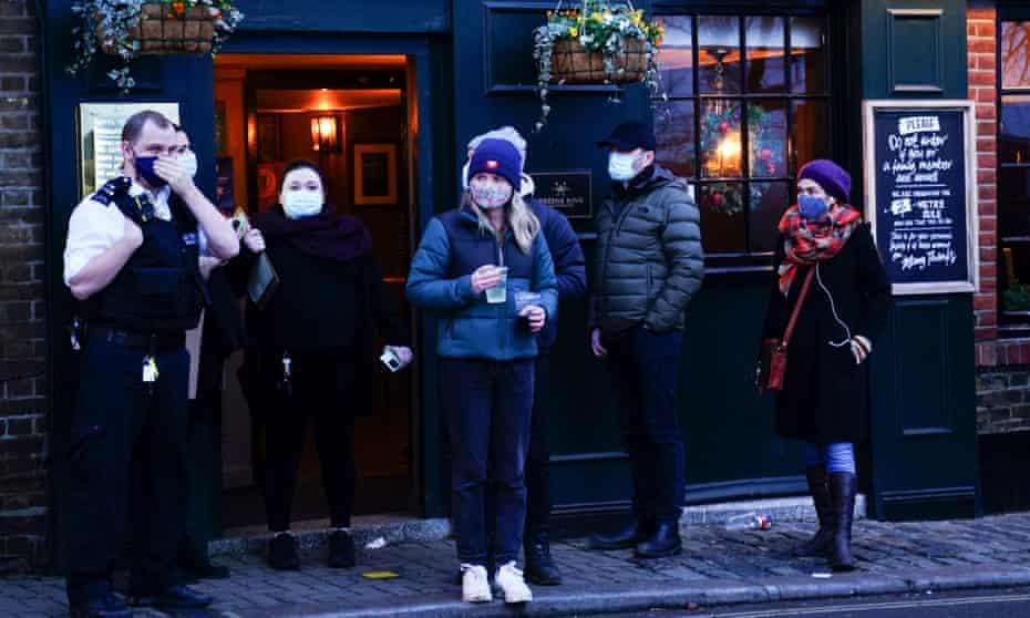 People queue outside a pub