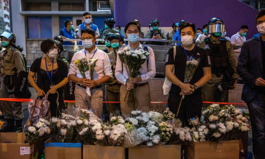Police personnel stand guard over a vigil for protesters who were injured during arrests in Hong Kong