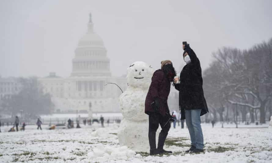 People pose for a selfie with a snowman at the National Mall near the US Capitol building in Washington DC Sunday.