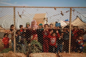 Displaced Syrian children stand outside their tents in a camp set up near the village of Kafr Lusin in Idlib's northern countryside near the border with Turkey.