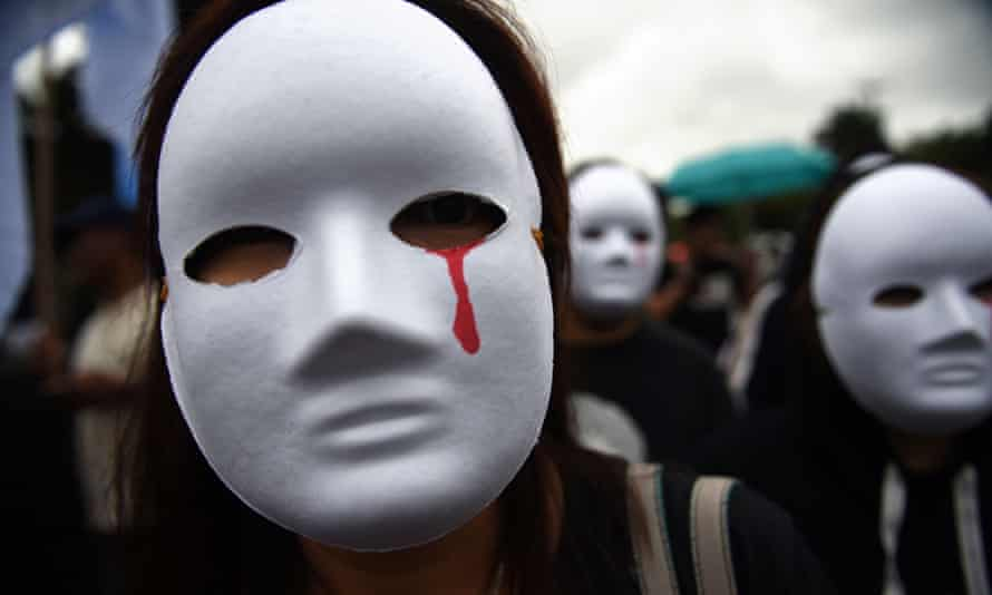 Protesters in Manila wear masks depicting victims of extra-judicial killings. The Philippines dropped the most places in the new Rule of Law Index.