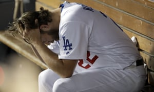 Clayton Kershaw sits in the dugout after giving up back-to-back home runs to the Washington Nationals in the 2019 playoffs