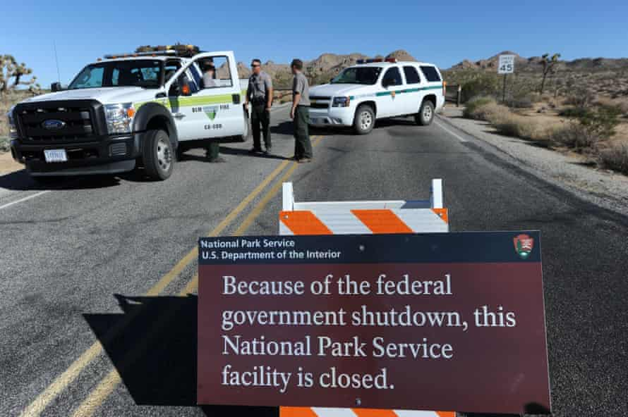 Park rangers stand at the closed gate to Joshua tree national park.