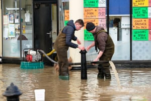 Shopkeepers struggle to pump out their premises in the Coleham district of Shrewsbury