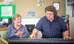 Glenda Roberts watches psychiatric nurse Edwin Humphreys playing keyboard