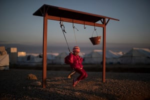 A displaced Iraqi girl, who fled fighting between Iraqi security forces and Isis militants, balances on a swing at the Hassan Sham camp, east of Mosul.